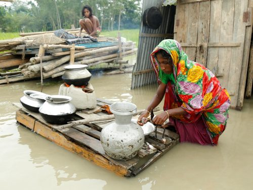 epa06147259 A woman cooks food in front of her flooded house near a river island formed from sedimentation, known as a 'char' at Mainkdir, Sariakandi, Bogra, Bangladesh, 16 August 2017. Flood victims are facing severe shortages of drinking water and food. Many flood victims have abandoned their homes along with their cattle, goats, to take shelter on embankments. At least 50 people have died as a result of the floods.  EPA/ABIR ABDULLAH