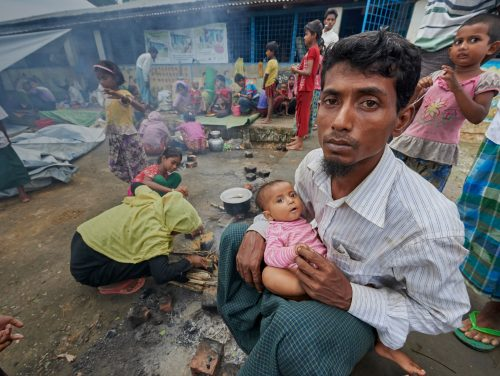 A Rohingya man, having just crossed the border from Myanmar, waits with a child and other members of his family to complete registration in the Kutupalong Refugee Camp near Cox's Bazar, Bangladesh, where members of the ACT Alliance provide humanitarian support for the refugees.  More than 600,000 Rohingya have fled government-sanctioned violence in Myanmar for safety in Bangladesh.